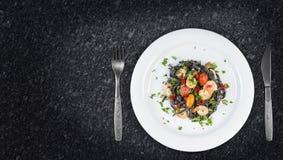 Svart pasta för tioarmad bläckfiskfärgpulverFettuccine med räkor eller körsbärsröda tomater för räkor, persilja, chili i vin och  royaltyfri foto