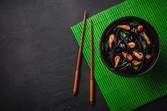 Svart pasta för tioarmad bläckfiskfärgpulverFettuccine med räkor eller räkor, persilja, chili i vin och smörsås Bästa sikt på gra royaltyfri bild