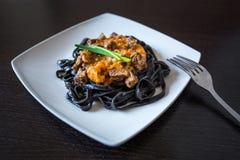 Svart pasta med bläckfiskfärgpulver Pasta av mannagryn för durumvete med tioarmad bläckfiskfärgpulver med sås för nötköt arkivfoton