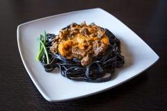 Svart pasta med bläckfiskfärgpulver Pasta av mannagryn för durumvete med tioarmad bläckfiskfärgpulver med sås för nötköt royaltyfri foto