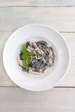 Svart pasta med champinjoner och kräm Arkivbild