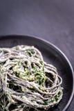 Svart pasta med spenat, mascarpone och parmesan Arkivfoton