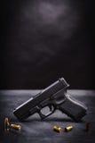 Svart pistol på en svart tabell Royaltyfria Bilder