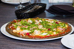 Svart pizza med ost- och bacon- och basilikatranbär i en caf Royaltyfri Foto