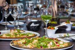 Svart pizza med ost- och bacon- och basilikatranbär i en caf Royaltyfria Bilder
