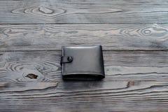 Svart plånbok för ` s för läderelegansmän på mörk träbakgrund Royaltyfria Bilder