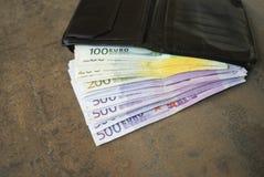 Svart plånbok med kontanta eurosedlar Fotografering för Bildbyråer
