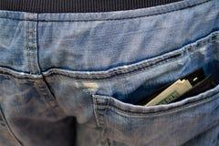 Svart plånbok med pengar som klibbar ut ur bakfickan av th Royaltyfri Bild