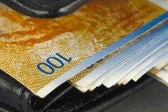 Svart plånbok med schweizisk franc royaltyfri bild