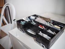 Svart plast- toolbox med proppar och skruvar på ett kabinett royaltyfria bilder