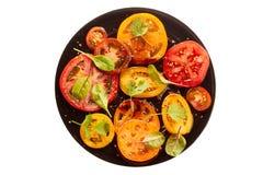 Svart platta av sallad med skivade tomater på vit Royaltyfria Foton
