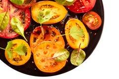 Svart platta av sallad med skivade tomater på vit Royaltyfri Fotografi