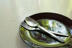Svart platta med skeden och gaffeln Arkivbild