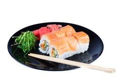 Svart platta med sushi och pinnar Arkivbilder
