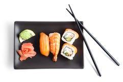 Svart platta med sushi som isoleras Arkivfoto