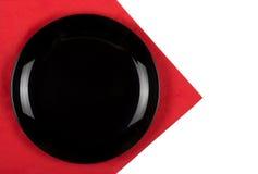 Svart platta på röd servett Royaltyfri Foto