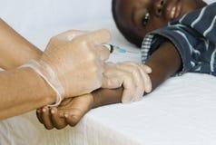 Svart pojke för afrikan som får en vaccinering från en vit medicinsk doktor royaltyfria bilder