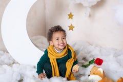 Svart pojke i en grön tröja och gult le för halsduk liten prince barnkakor ?ter scandinavia Barns rum för t royaltyfria bilder