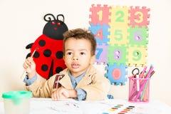 Svart pojketeckning för afrikansk amerikan i förträning på tabellen i dagis Arkivfoton