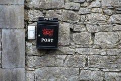 Svart Postbox på en stenvägg Arkivbilder