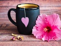 Svart rånar av te med en rosa hjärta på en rosa hibiskusblomma för rad på mörk wood bakgrund Royaltyfria Foton