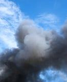 Svart rök och blå himmel Arkivfoto