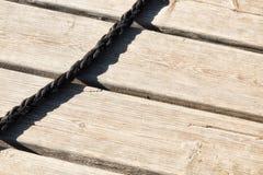 Svart rep på hamnträplankor royaltyfri fotografi