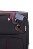 Svart resväska med solglasögon och pass Arkivfoto
