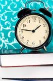 Svart retro klocka på böckerna Royaltyfri Foto