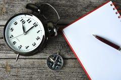 Svart ringklocka, penna och anteckningsbok på den rostiga trätabellen Arkivbilder