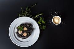 Svart risotto med örter och parmesan fotografering för bildbyråer
