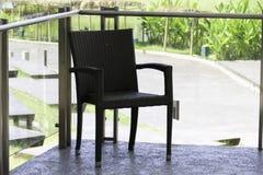 Svart rottingstol på terrassen Fotografering för Bildbyråer