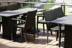 Svart rottingtabell och stol på terrassen Royaltyfria Bilder