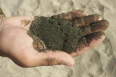 Svart sand i hand arkivbilder
