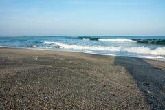 Svart sand och vita vågor på vintern sätter på land i Pomorie, Bulgarien Arkivbilder