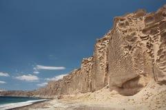 Svart sandstrand med vind sned klippor arkivbilder