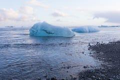 Svart sandstrand och is som bryter från isberget Royaltyfria Foton