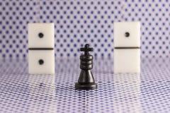 Svart schackkonung och tärning för domino på en suddig bakgrund av den tillbaka sidan av att spela kort Arkivbilder
