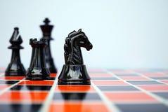 Svart schackriddare på schackbräde Arkivfoton