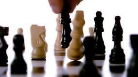 Svart schackstycke som knackar över vit arkivfilmer