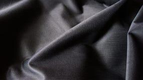 Svart silkeslen sammansatt bakgrund för textur för torkduketygkurvor Arkivbild