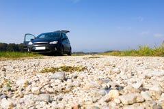 Svart skåpbil som parkeras på grusvägen, låg vinkel, copyspace royaltyfria foton