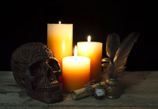 Svart skalle med stearinljus och klockan Royaltyfria Bilder