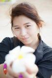 Svart skjorta för asiatiska kvinnor. Hållande vit blomma. Royaltyfri Foto