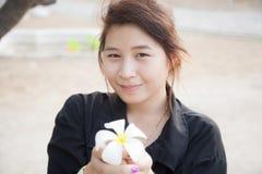 Svart skjorta för asiatiska kvinnor. Hållande vit blomma. Royaltyfria Foton