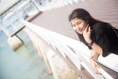 Svart skjorta för asiatiska kvinnor som står träterrassen Arkivbild