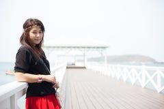 Svart skjorta för asiatiska kvinnor som står träterrassen Royaltyfri Bild