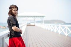 Svart skjorta för asiatiska kvinnor som står träterrassen Royaltyfria Bilder