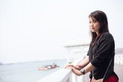 Svart skjorta för asiatiska kvinnor som står träterrassen Arkivfoton