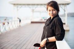 Svart skjorta för asiatiska kvinnor som står träterrassen Royaltyfri Fotografi